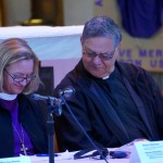 Bishop Mary and Bishop Richard look up the words for the Prayer of St. Francis.