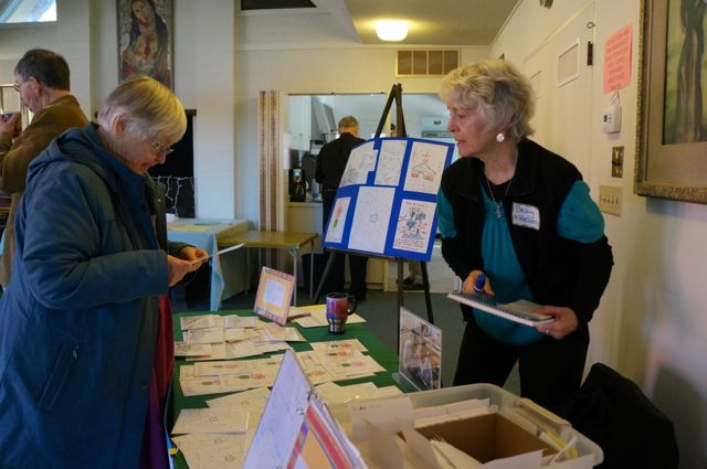 Becky Mikkelsen shows greeting cards created by students in the Diocese of Western Tanganyika to Margaret Markham.